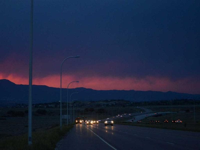 The front range glows an eerie red from the smoke of the Black Forest Fire which continues to burn out of control for a second straight day near Colorado Springs. The fire has consumed 11,500 acres. It has destroyed 92 homes and damaged others. (AP)