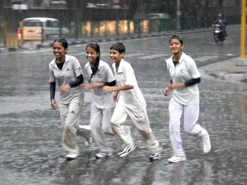 Children run along a road during a heavy rain shower in Chandigarh. Reuters photo
