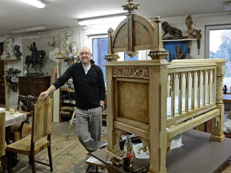 Dariusz Bergier poses in his studio in Lodz next to a cradle he designed, which he plans to make a gift of to Kate Middleton and Prince William for their child. AFP