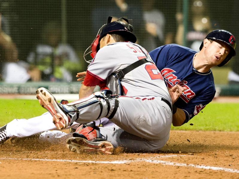Drew Stubbs of the Cleveland Indians slides into catcher Kurt Suzuki of the Washington Nationals to score the game-winning run in the ninth inning at Progressive Field in Cleveland, Ohio. AFP