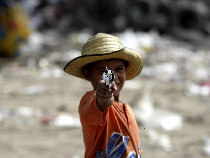 A garbage collector poses for a picture with a toy gun at the municipal dump site, on the outskirts of Tegucigalpa. Reuters
