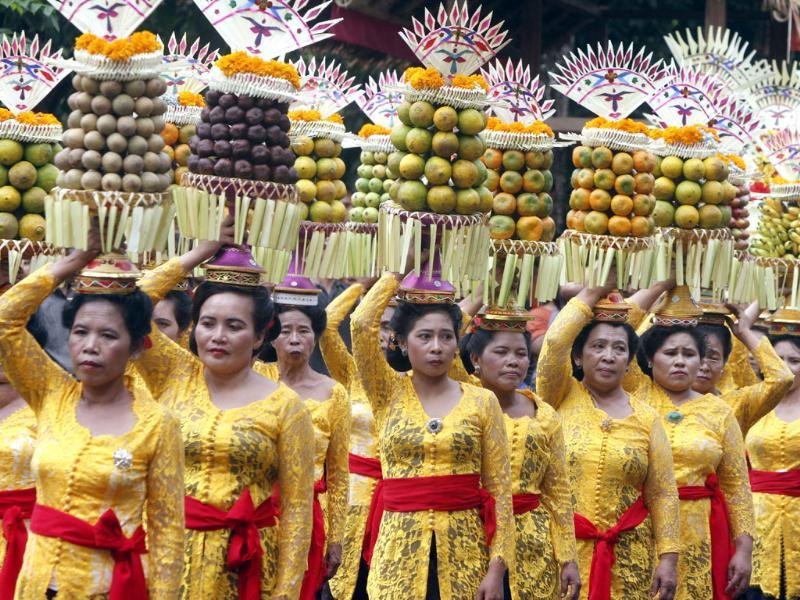 Indonesian women in traditional outfit carry offering on their heads during a parade to mark the 35th Bali Arts Festival in Denpasar, Bali, Indonesia. Photo: AP/Firdia Lisnawati
