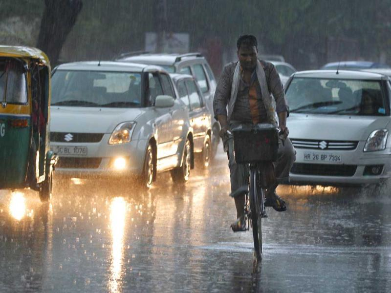 A cyclist navigates through the traffic during the first monsoon shower of the season near Mehrauli in New Delhi. HT/Arvind Yadav