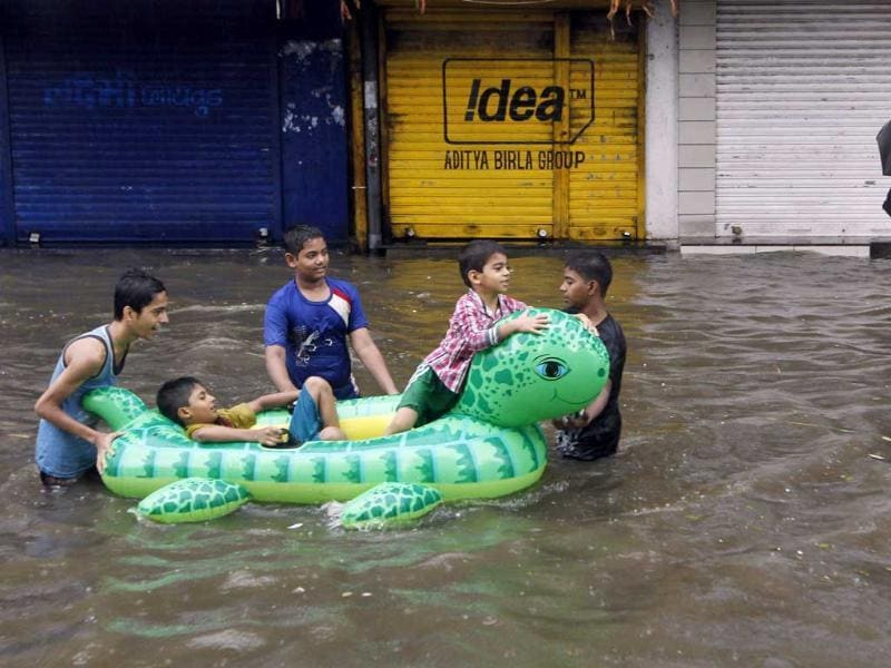 Children enjoy the rain floating on an inflated tube on a flooded street after heavy monsoon rains in Mumbai. AP