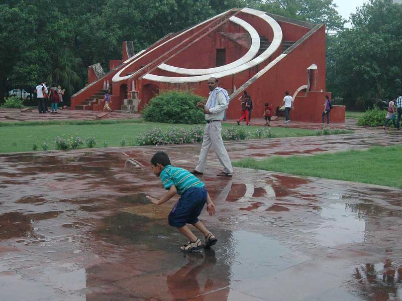 A child playing in a puddle of water after rain, at Jantar Mantar in New Delhi. UNI