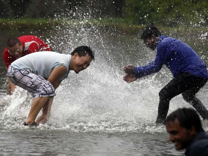 People having fun in a water puddle near Rajghat lawn during a spell pre-monsoon rain in New Delhi. HT/Raj K Raj