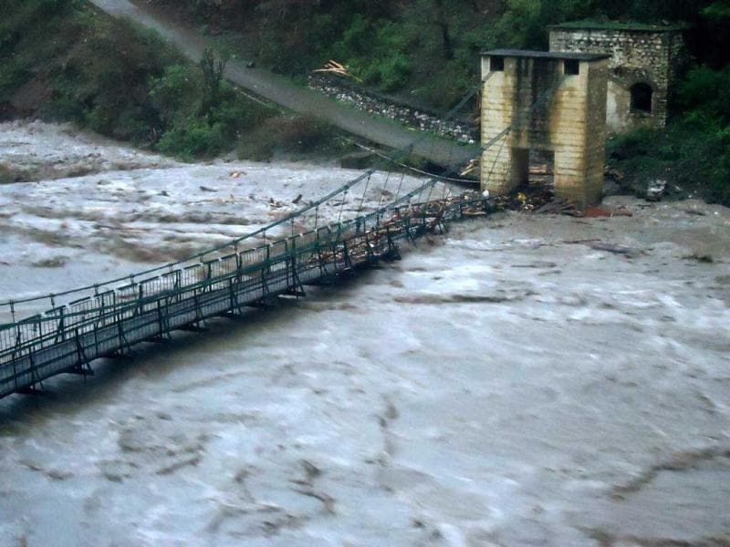 A view of the overflowing Mandakini River damaging the bridge over it in Kedarnath Valley in Rudraprayag district on Monday following incessant rains.