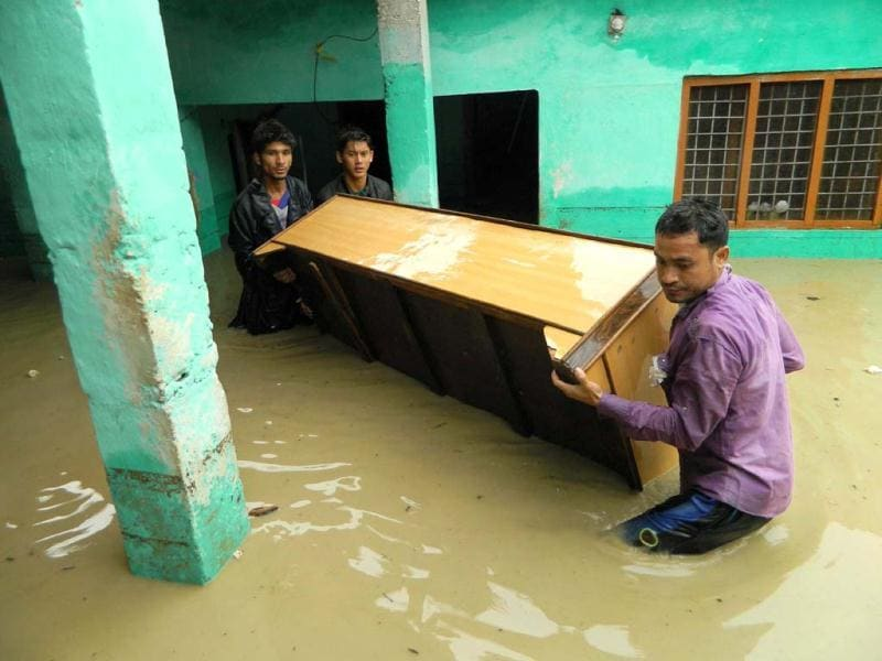People move furniture as homes floods due to the heavy rains in the northern state of Uttarakhand.