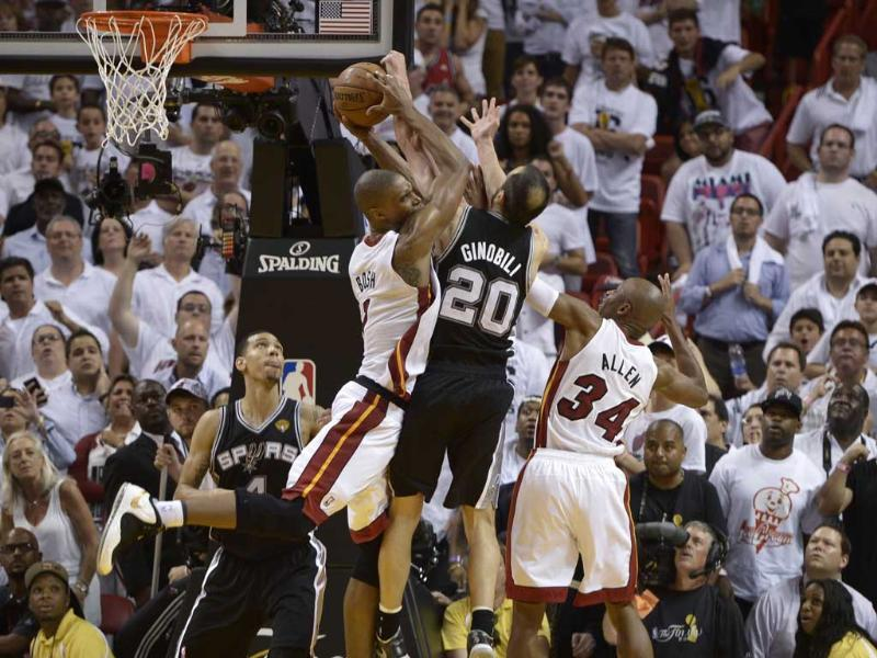 Chris Bosh (L) of the Miami Heat snares a rebound before teammate Ray Allen (R) against Manu Ginobili (C) of the San Antonio Spurs during overtime in Game 6 of the NBA Finals against the Miami Heat at the American Airlines Arena in Miami, Florida. AFP