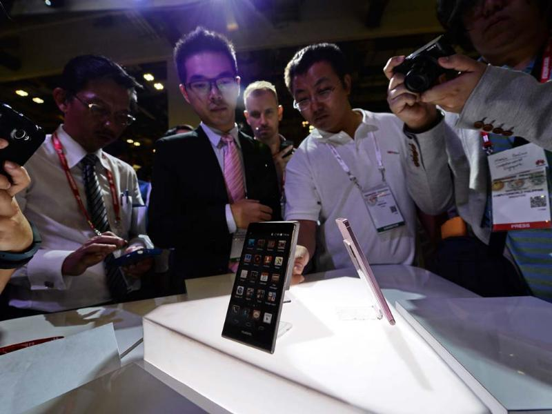 Visitors look at Huawei's Ascend P6 phone, billed as the world's thinnest smartphone, at the CommunicAsia telecom and broadcast event in Singapore. Photo: AFP/Roslan Rahman