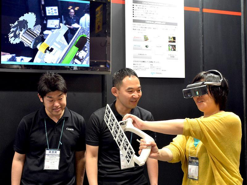 A visitor wears Japanese high-tech giant Canon's see-through head mount display (HMD)