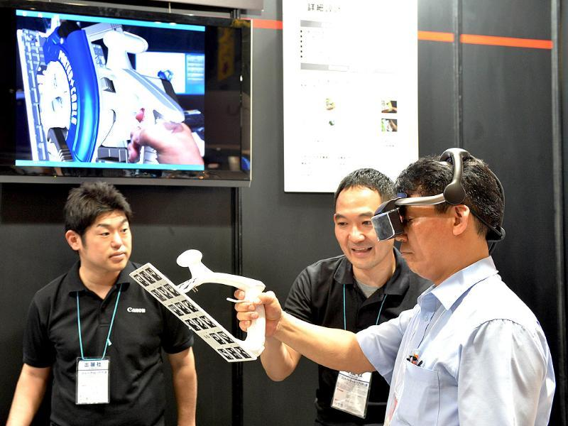 A visitor wears Japanese high-tech giant Canon's see-through head mount display