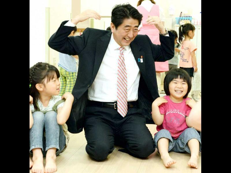 Japan's Prime Minister Shinzo Abe (C) plays with children as he inspects a daycare center in Yokohama, south of Tokyo. (Reuters)