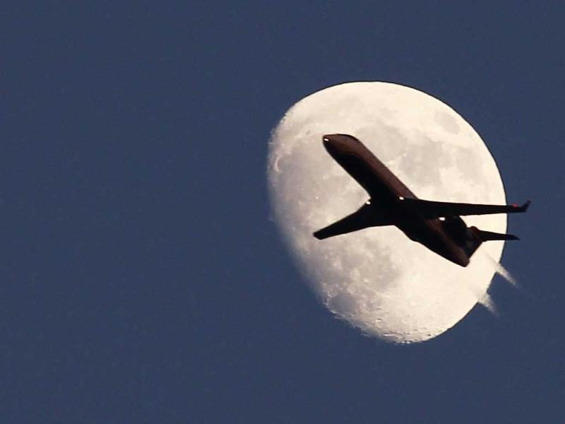 An airplane passes by the moon in its waxing gibbous phase in the sky over Hoboken, New Jersey. (Reuters)