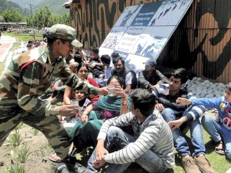 Army personnel distribute water to stranded pilgrims after they were rescued from a flood-hit area at Harsil in Uttarakhand. PTI Photo