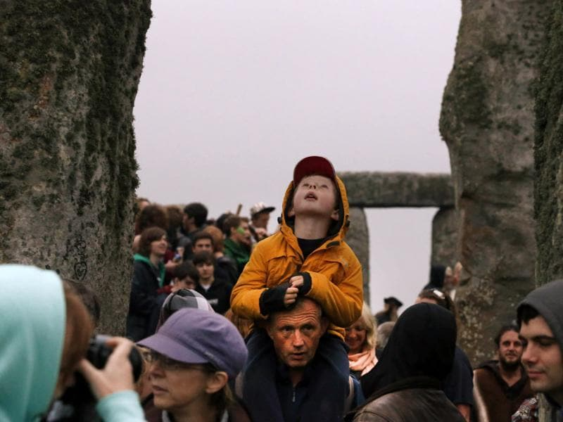 People walk during the summer solstice shortly after 04:52 am at the prehistoric Stonehenge monument, near Salisbury, England. AP