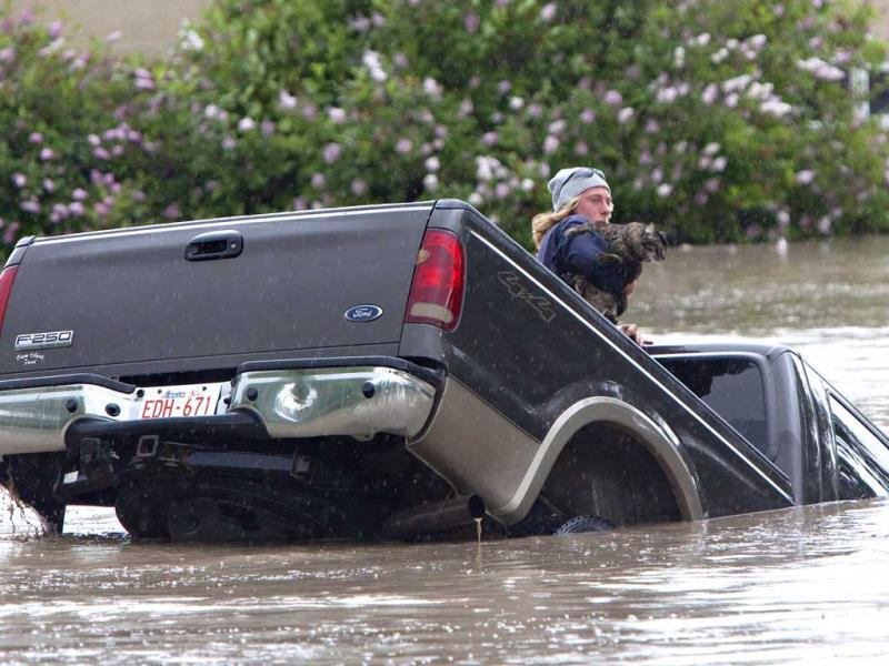 Kevan Yeats crawls out the back window of his pick up truck with his cat Momo as the flood waters sweep him downstream after submerging his truck in High River, Alberta after the Highwood River overflowed its banks. (AP)