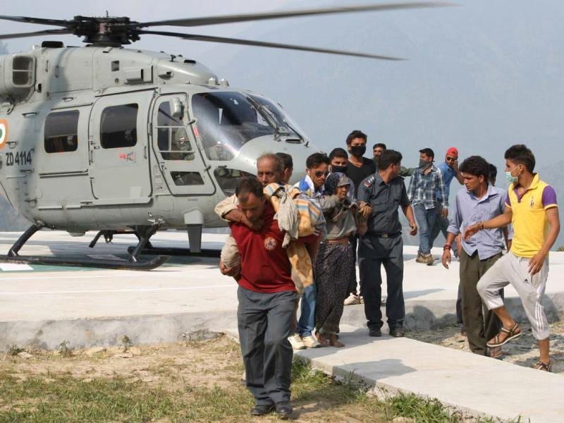 Rescued flood evacuees alight from an Indian Air Force HAL Dhruv utility helicopter flying rescue sorties over the Kedarnath valley in Uttarakhand, in Ghauri Kund. (AFP/Ministry of Defence/Gurudutt Mehra)