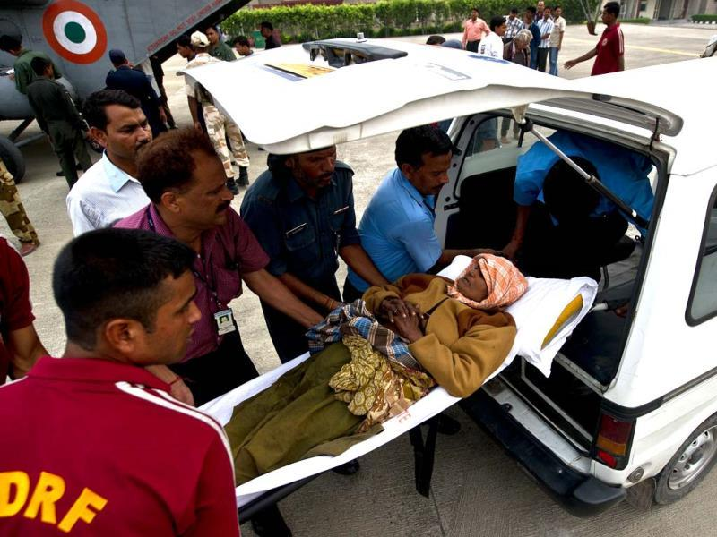 Disaster relief personnel assist an elderly woman into an ambulance after being evacuated from flood-hit areas at the Jolly Grant Airport in Dehradun. (AFP/Ministry of Defence/Gurudutt Mehra)