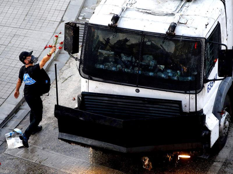 A protestor throws flowers towards a water cannon truck at Taksim Square in Istanbul. Turkish riot police fired water cannon and teargas to disperse thousands of anti-government demonstrators in central Istanbul. (Reuters)