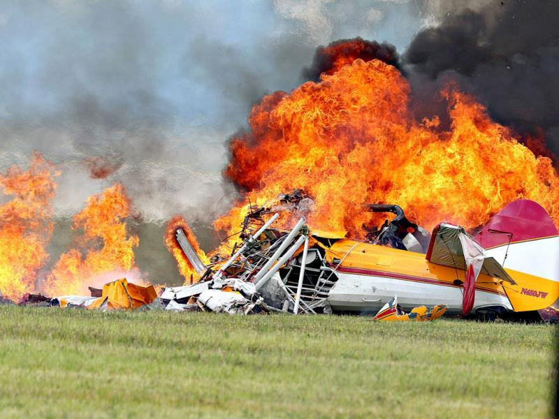 Flames erupt from a plane after a stunt plane crashed while performing with a wing walker at the Vectren Air Show in Dayton, Ohio. The crash killed the pilot and the wing walker instantly. (AP)