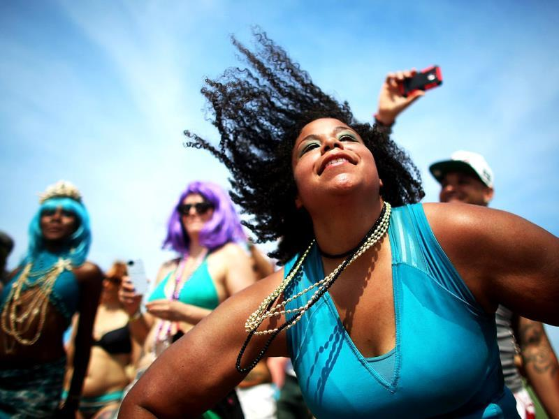Revelers dance on the beach at the 2013 Mermaid Parade at Coney Island in the Brooklyn borough of New York City. (AFP)