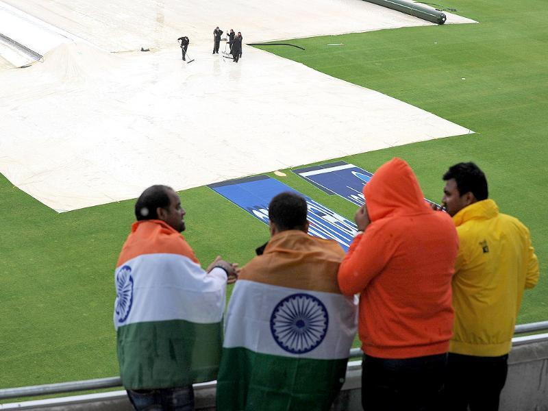 Spectators watch groundstaff removing water from the the covers as rain delays the start of play in the 2013 ICC Champions Trophy final match in Birmingham. AFP