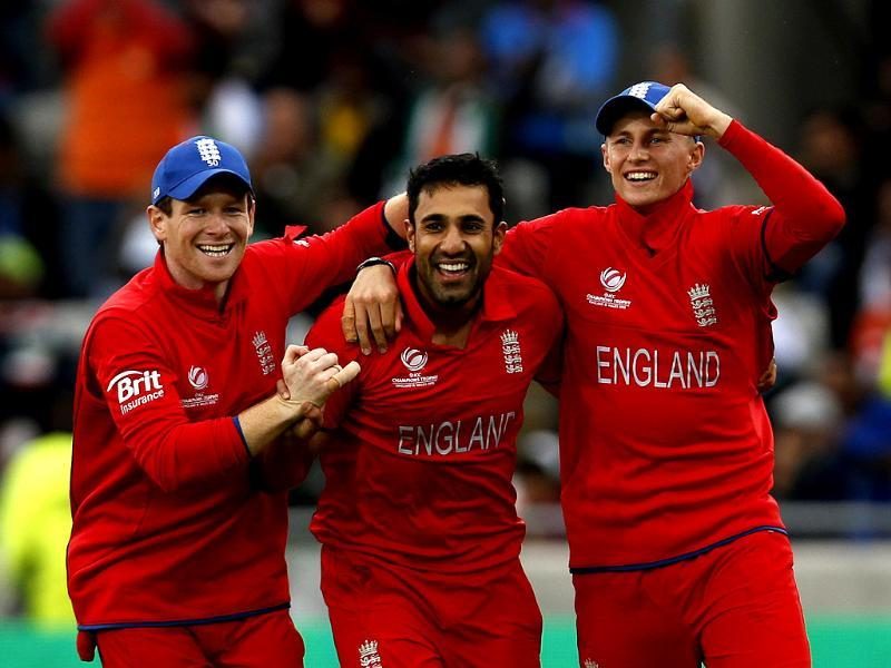 England's Ravi Bopara celebrates the wicket MS Dhoni with teammates Eoin Morgan and Joe Root during their ICC Champions Trophy final match at Edgbaston ground in Birmingham. AP