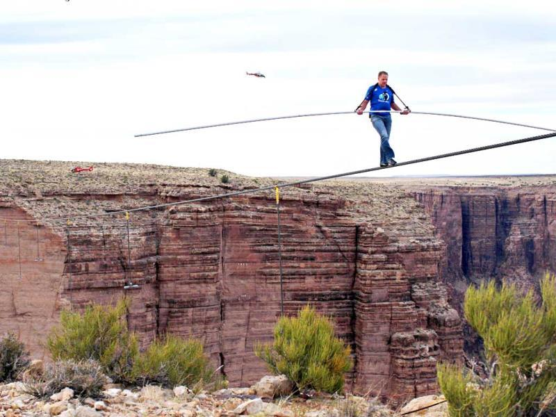 Aerialist Nik Wallenda near the end of his quarter mile walk over the Little Colorado River Gorge in northeastern Arizona. The daredevil successfully traversed the tightrope strung 1,500 feet above the chasm near the Grand Canyon in just more than 22 minutes, pausing and crouching twice as winds whipped around him and the cable swayed. (AP)