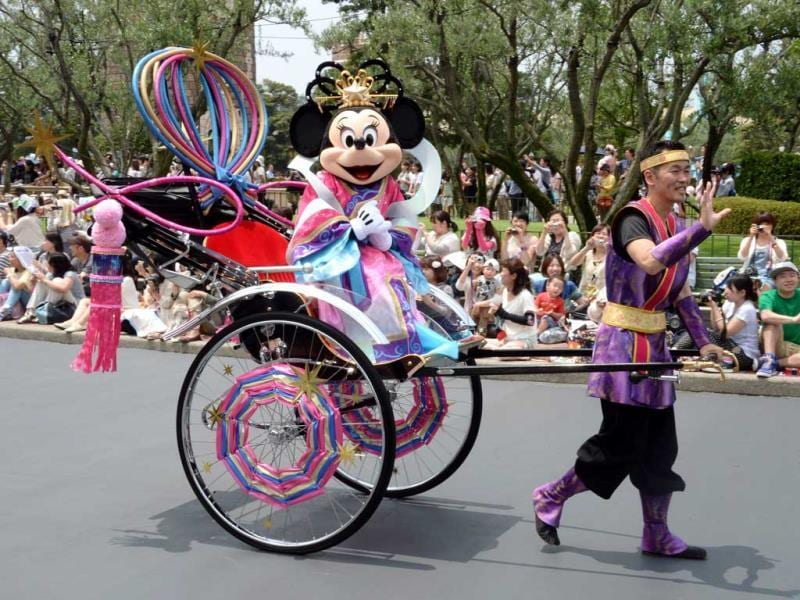Disney character Minnie Mouse, who represents Vega the Weaver, waves to spectators from rickshaw to celebrate