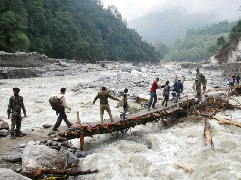 Indian army personnel help stranded people cross a flooded river after heavy rains in the Himalayan state of Uttarakhand. (Reuters)