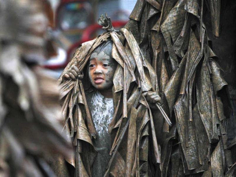 A boy, covered with mud and dried banana leaves, walks around the village to ask for candles before attending a mass celebrating the feast day of the Catholic patron Saint John the Baptist in the village of Bibiclat, Nueva Ecija, north of Manila. (Reuters)