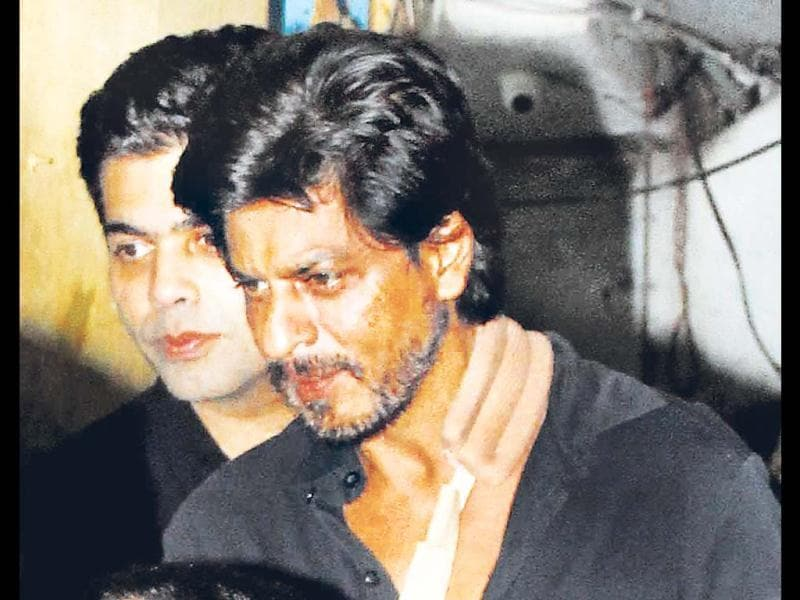 Run down but still partying! SRK with arm in a sling and Karan Johar by his side spotted at a dinner party.
