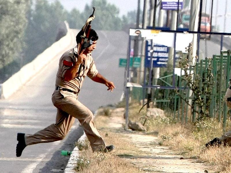 Policemen run to take positions during an encounter after militants attacked an Army convoy in Srinagar on Monday. PTI