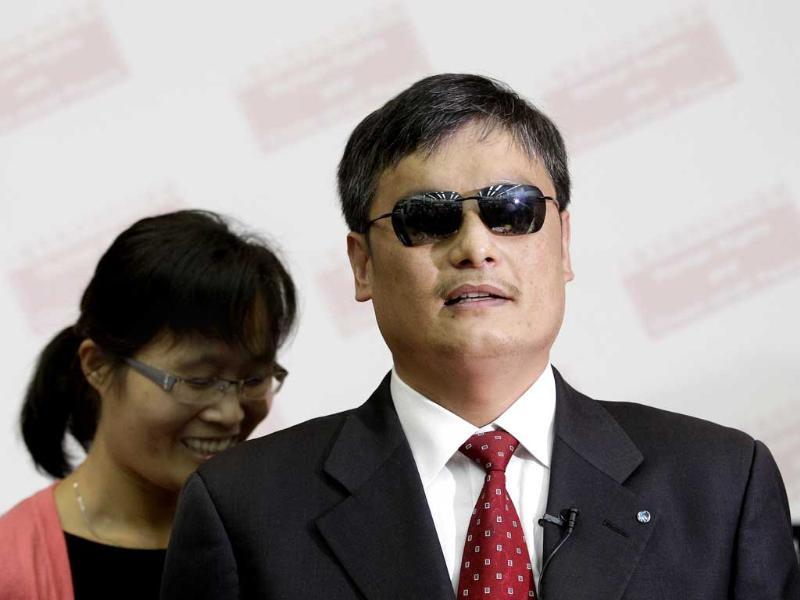 Chinese dissident Chen Guangcheng (R) and his wife Yuan Weijing prepare to leave after Chen's speech on