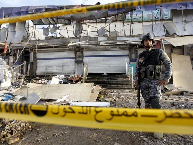 An Iraqi policeman stands guard at the site of a car bomb attack in Baghdad. 10 car bombs exploded across the Iraqi capital on Monday, killing nearly 40 people. Reuters
