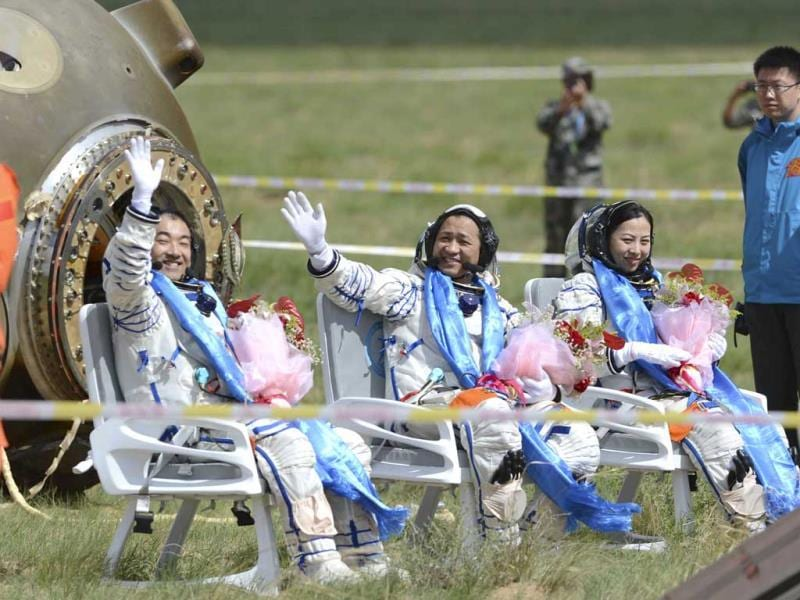 In this photo released by China's Xinhua News Agency, astronauts Zhang Xiaoguang, Nie Haisheng and Wang Yaping, from left to right, wave after getting out of the re-entry capsule of China's Shenzhou 10 spacecraft following its successful landing at the main landing site in Siziwang Banner, north China's Inner Mongolia Autonomous Region. (AP)