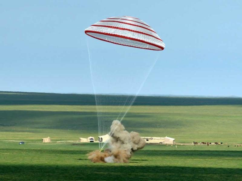 In this photo released by China's Xinhua News Agency, the re-entry capsule of China's Shenzhou 10 spacecraft lands in Siziwang Banner, north China's Inner Mongolia Autonomous Region. The space capsule with three astronauts has safely landed on grasslands in northern China after a 15-day trip to the country's prototype space station. (AP)