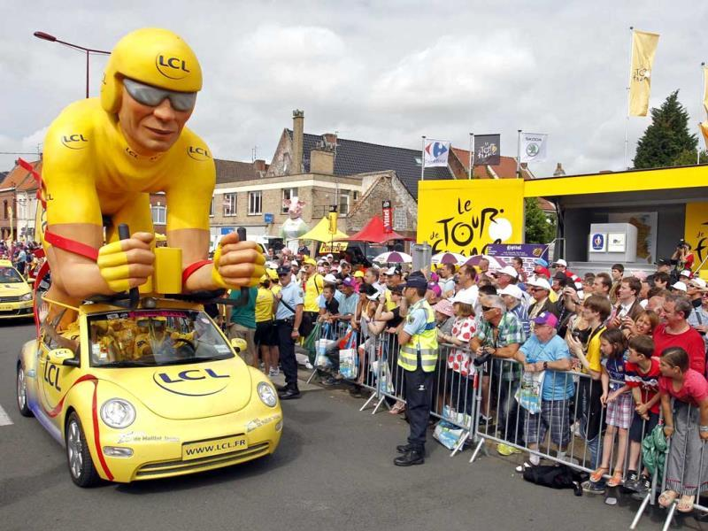 A Le Credit Lyonnais (LCL) vehicle from the publicity caravan of the Tour de France travels past spectators at the start of the third stage of the 99th Tour de France cycling race between Orchies and Boulogne-sur-Mer. (Reuters)