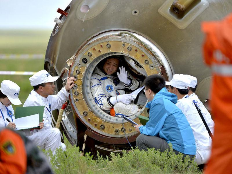 Chinese astronaut Nie Haisheng waves before getting out of the re-entry capsule of China's Shenzhou-10 spacecraft after it landed at its main landing site in Inner Mongolia Autonomous Region. (Retuers photo)