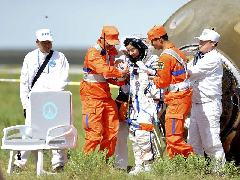 Chinese astronaut Wang Yaping (C) goes out of the re-entry capsule of China's Shenzhou 10 spacecraft after its successful landing at the main landing site in Siziwang Banner, north China's Inner Mongolia Autonomous. (AP photo)