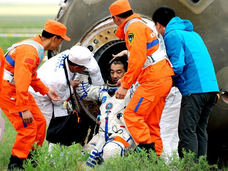 Chinese astronaut Zhang Xiaoguang (C) is helped by technicians to get out from the Shenzhou-10 spacecraft after it landed in the grasslands of north China's Inner Mongolia region. (AFP photo)