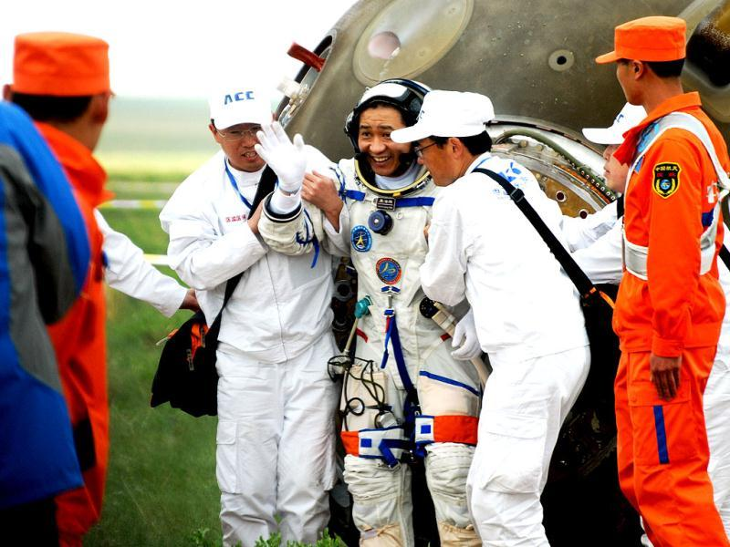 Chinese astronaut Nie Haisheng (C) waves after getting out from the Shenzhou-10 spacecraft after it landed in the grasslands of north China's Inner Mongolia. (AFP photo)