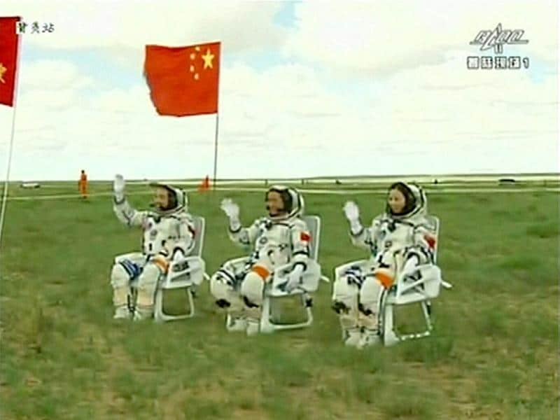 Astronauts (L-R) Zhang Xiaoguang, Nie Haisheng and Wang Yaping wave after returning to earth in the re-entry capsule of China's Shenzhou-10 spacecraft at its main landing site in north China's Inner Mongolia Autonomous Region. (Reuters/CCTV)