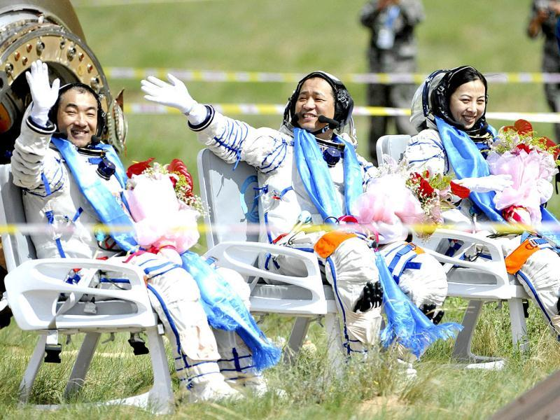 Astronauts (L-R) Zhang Xiaoguang, Nie Haisheng and Wang Yaping wave after returning to earth in the re-entry capsule of China's Shenzhou-10 spacecraft at its main landing site in north China's Inner Mongolia Autonomous Region. (Reuters photo)