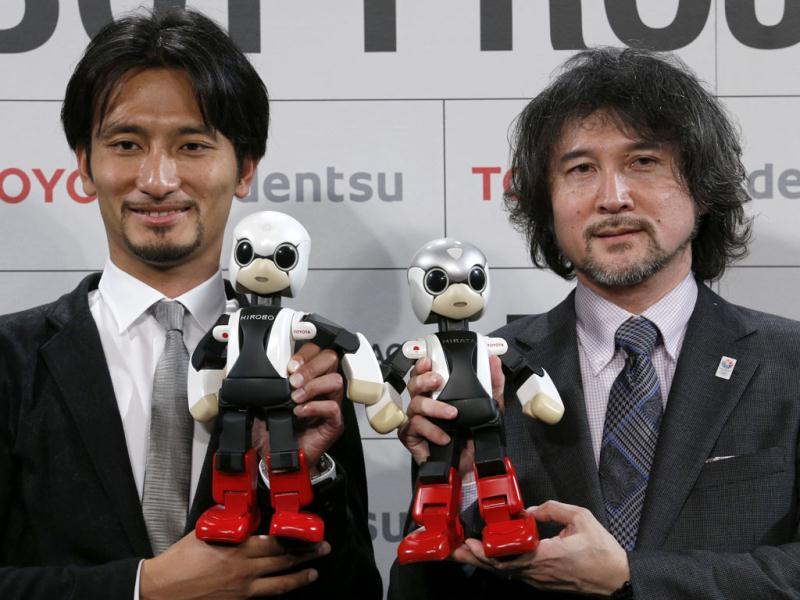 Humanoid communication robots, Kirobo, bottom left, and Mirata, bottom right, are held by Tomotaka Takahashi, left, CEO of Robo Garage Co. and project associate professor from the University of Tokyo, and Fuminori Kataoka, project general manager from Toyota Motor Corp., during a press unveiling in Tokyo. (AP Photo)