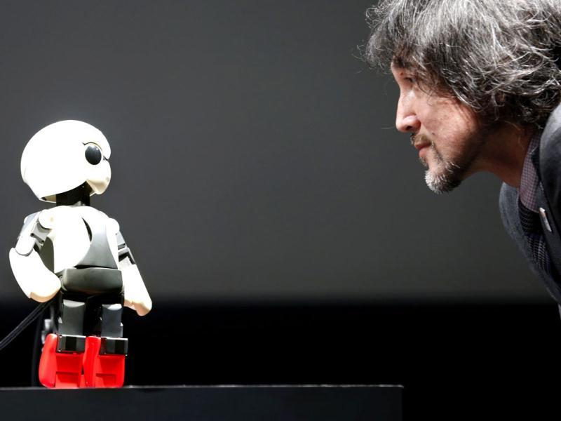 Humanoid communication robot Kirobo, left, talks with Fuminori Kataoka, project general manager from Toyota Motor Corp., during a press unveiling in Tokyo. (AP Photo)