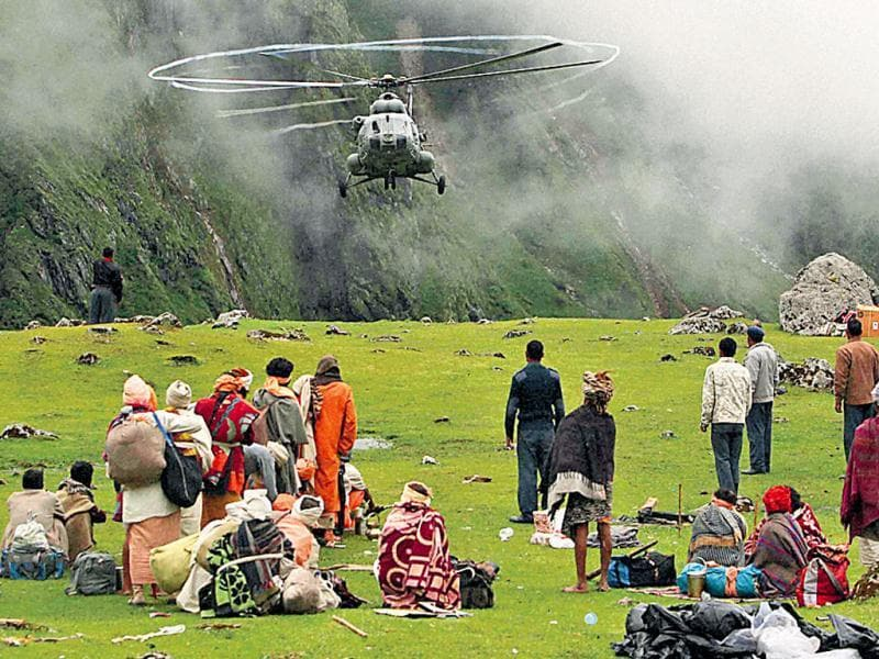 Pilgrims look on as an IAF helicopter lands near Kedarnath temple in a rescue effort. (PTI Photo)