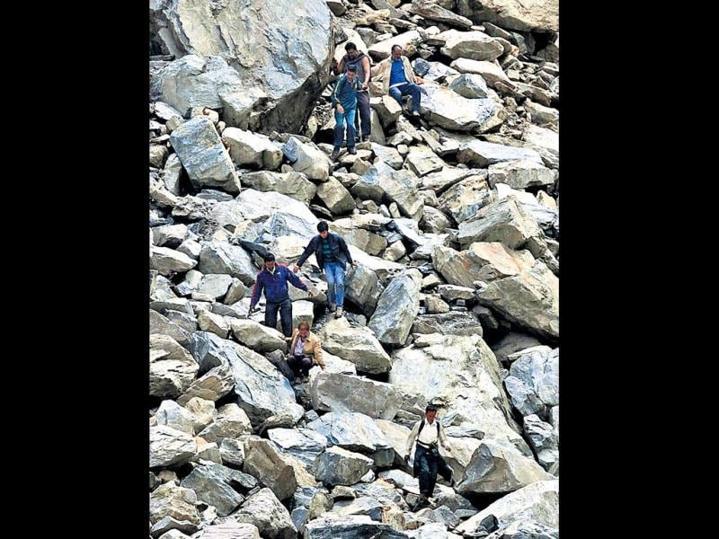 People stuck in Gaurikund coming down through the remains of the road in Uttarakhand. (HT Photo)