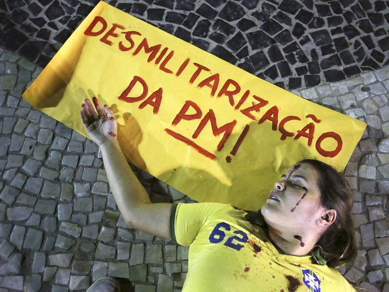 A demonstrator, with fake blood dripped onto herself, lies on the ground during a protest against Brazilian military police at the Copacabana beach in Rio de Janeiro. Reuters